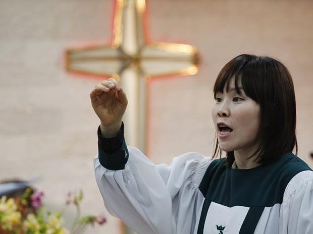 Uma desertora norte-acoreano, que vive em Seul, conduz um coral culto. Pessoas rezavam pela reunificação das Coreias (Foto: Reuters)