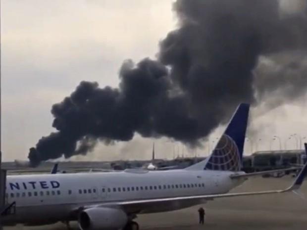 Imagem tirada de vídeo mostra fumaça saindo de avião na pista do Aeroporto O'Hare, em Chicago, nesta sexta-feira (28) (Foto: Courtesy of Robocast.com/Handout via REUTERS)