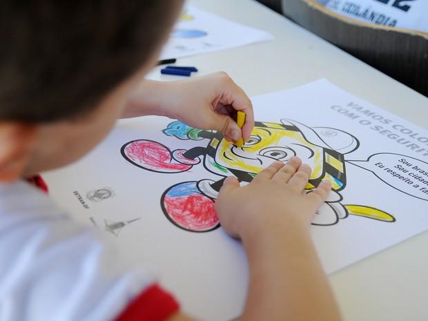 Estudante de escola pública usa giz de cera para colorir desenho  (Foto: Pedro Ventura/Agência Brasília)