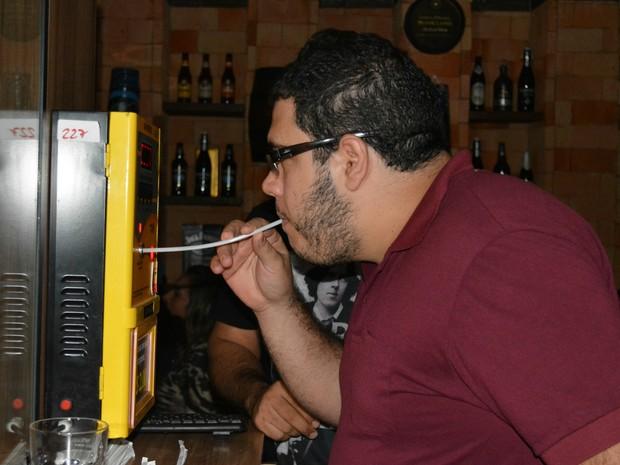 Funcionário público realiza o teste do bafômetro para saber a quantidade de álcool por litro de ar expelido (Foto: Mary Porfiro/G1)