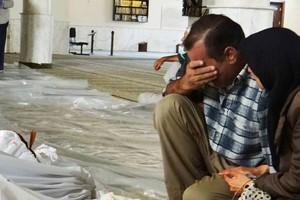 Cidadãos sírios choram sobre os corpos das vítimas do bombardeio nesta quarta-feira (21) na periferia de Damasco (Foto: AP Photo/Local Committee of Arbeen)