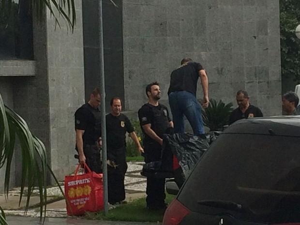 Policiais carregam carro que seguirá para o Paraná com malotes com documentos (Foto: Glauco Araújo/G1)