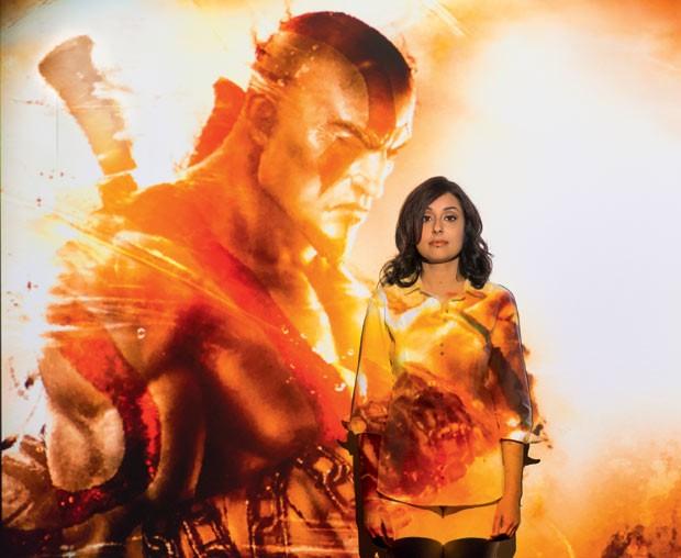 Daniela, 25, sofre assédio pesado enquanto joga. Na indústria de videogames, tramas com poucas personagens femininas, como a de God of War (na projeção), são comuns (Foto: Gabriel Rinaldi)