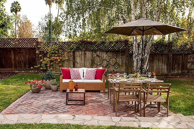 A mesa e o pequeno sofá são um verdadeiro convite para tomar um café na área externa, repleta de plantas e árvores. Um sonho! (Foto: Divulgação)