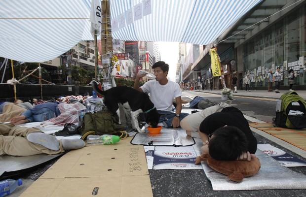 Manifestantes pró-democracia descansam em principal rua do distrito de Mongkok, nesta sexta-feira (10) (Foto: Liau Chung-ren/Reuters)