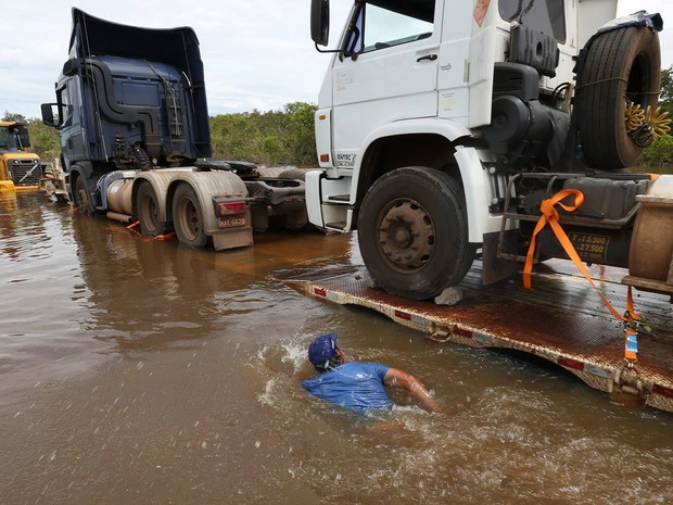 Homem nada ao lado de carretas na BR-364, inundada pelo Rio Madeira  (Foto: Sérgio Vale/Secom Acre)