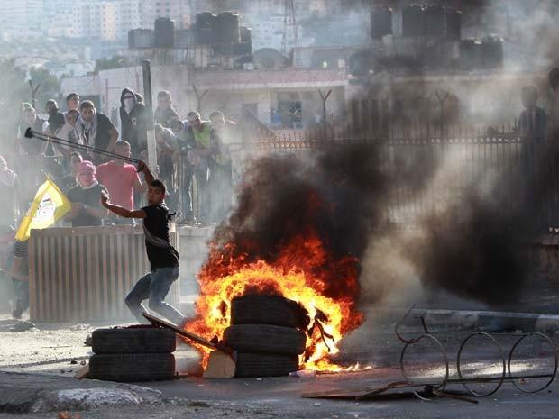 Adolescente joga pedras em soldados israelenses durante protesto nesta terça-feira (6) em Belém (Foto: AFP PHOTO / MUSA AL-SHAER)