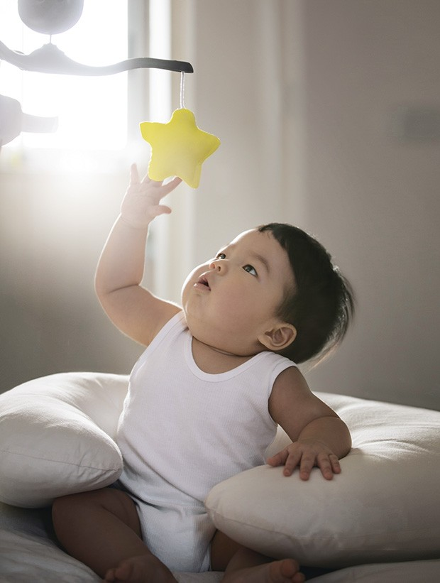 """Asian toddler boy sitting on bed reaching out to catch a rotating toy star. Conceptual baby photo, """"Reaching out to the star"""". (Foto: Getty Images)"""