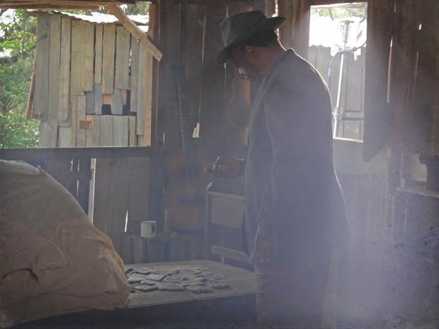 Afonso esconde dinheiro debaixo do colchão (Foto: Lado a Lado/Tv Globo)