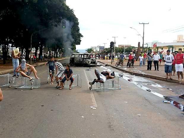 Manifestantes se sentam em carrinhos de compras; ao fundo, veículo incendiado durante protesto por fechamento de supermercado (Foto: Aldair Fernando/G1)