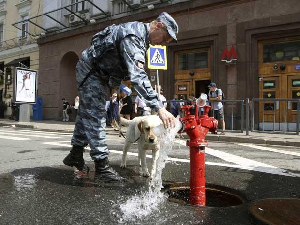 Um policial dá água a seu cão-farejador. (Foto: Denis Tyrin / AP Photo)