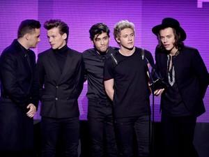 Os integrantes do One Direction (a partir da esq.), Liam Payne, Louis Tomlinson, Zayn Malik, Niall Horan e Harry Styles, recebem o prêmio de melhor álbum de pop/rock no American Music Awards pelo disco 'Midnight mmories' (Foto: Kevin Winter/Getty Images/AFP)