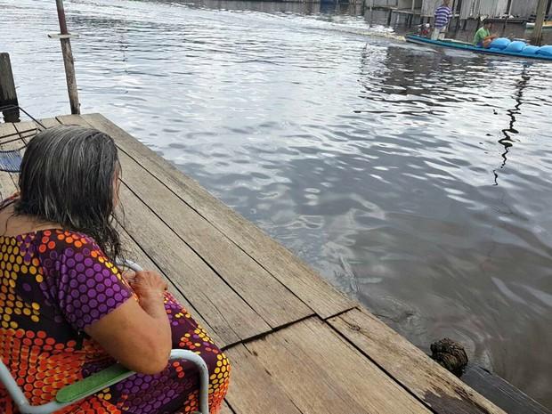 Dona Osmarina acredita que o rio deve subir ainda mais nos próximos dias e se preocupa  (Foto: Anny Barbosa/G1)