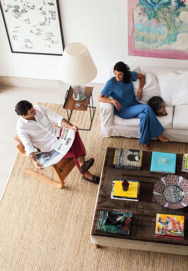 O casal com o yorkshire Bartô no living decorado com enorme pufe John Graz, usado como apoio para livros de arte, e tapete By Kamy Styling: Raquel Kavati (Foto: Deco Cury)
