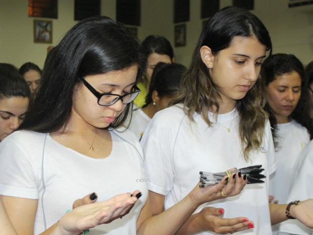 Estudante levou canetas para receber benção de padre durante missa especial (Foto: Gabriela Pavão/ G1 MS)