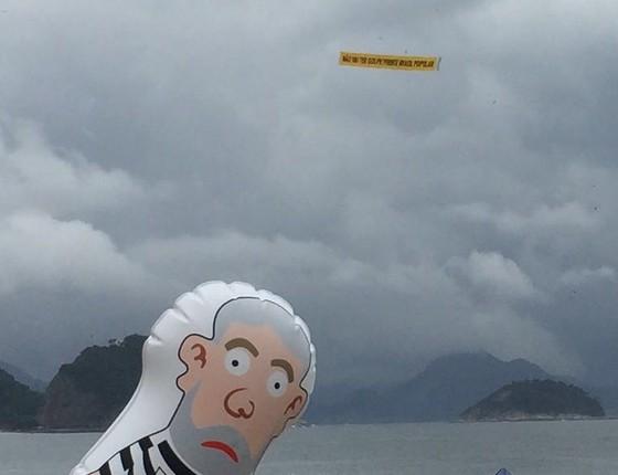 """Manifestação em Copacabana, Rio de Janeiro. Em foco, o """"Pixuleco"""", boneco anti-governo mostrando o ex-presidente Lula vestido de presidiário. Ao fundo, um avião mostra a faixa """"Não vai ter golpe"""", slogan de grupos pró-governo (Foto: Samantha Lima/ÉPOCA)"""