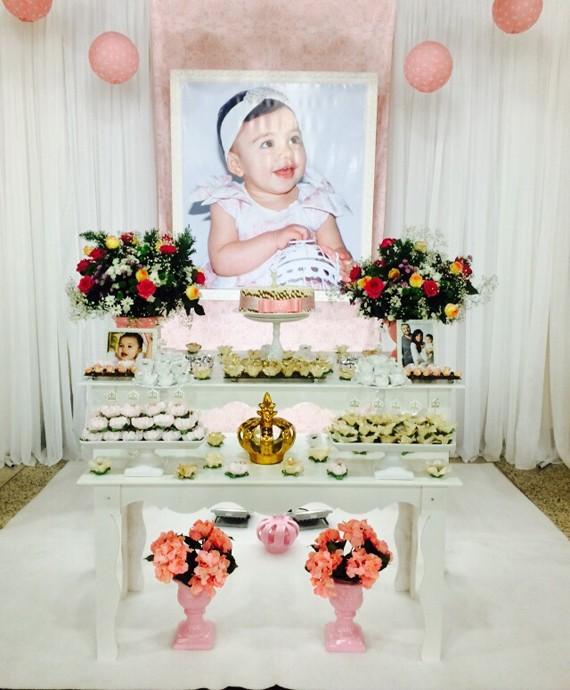 A mesa do bolo decorada com flores, fotos da família e uma coroa (Foto: Arquivo Pessoal)