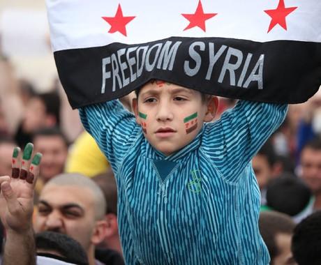 Garoto levanta bandeira da síria em manifestação contra o ditador Bashar al-Assad e em comemoração do segundo ano de revolta na Síria (Foto: Mohammad Hannon/AP)