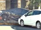 Carro fica pendurado em barra de ferro colocada em calçada após batida