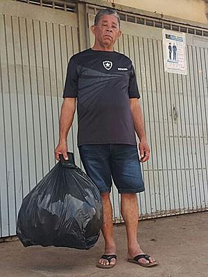 O pedreiro aposentado Benício Eleutério com a carteira que perdeu ao jogar fora saco de lixo e que lhe foi devolvida por estudante (Foto: Raquel Morais/G1)