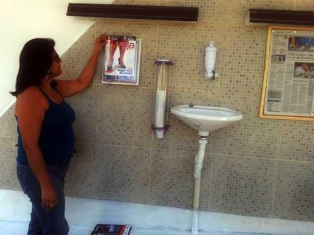A doméstica Mariluci Raimundo arruma as revistas doadas no ponto de ônibus vip (Foto: Luciano Calafiori/G1)