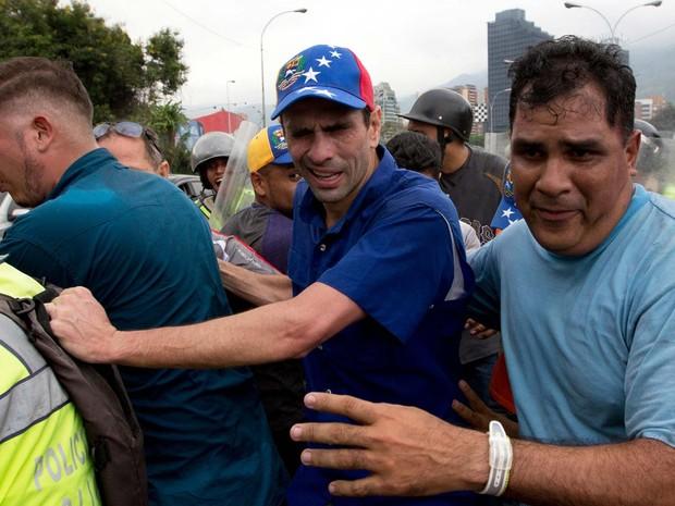 Líder opositor Henrique Capriles reage aos efeitos do gás lacrimogêneo lançado para reprimir manifestação contra o governo nesta quarta-feira (11) em Caracas (Foto: AP Photo/Fernando Llano)