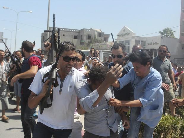 Policiais escoltam um homem suspeito de estar envolvido no atentado a um hotel em Sousse, na Tunísia. Pelo menos 27 pessoas , incluindo turistas estrangeiros, foram mortos quando pelo menos um atirador abriu fogo no hotel (Foto: Amine Ben Aziza/Reuters)