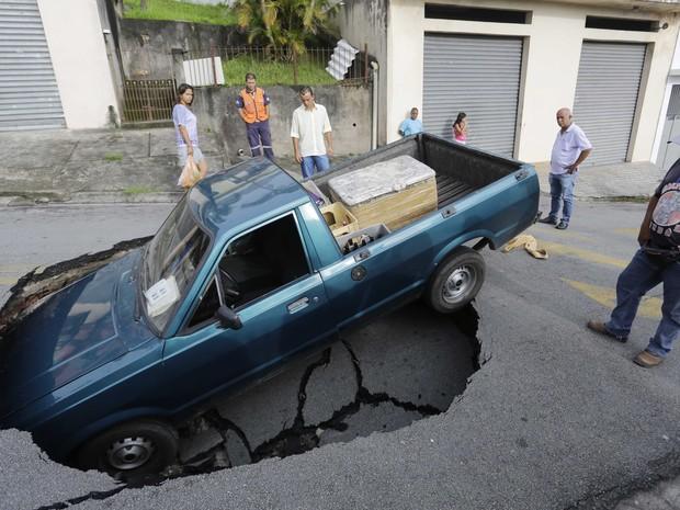Carro cai em buraco em Itapecerica da Serra, Grande São Paulo. Ninguém ficou ferido; asfalto cedeu após vazamento de água. (Foto: Nelson Antoine/Fotoarena/Estadão Conteúdo)