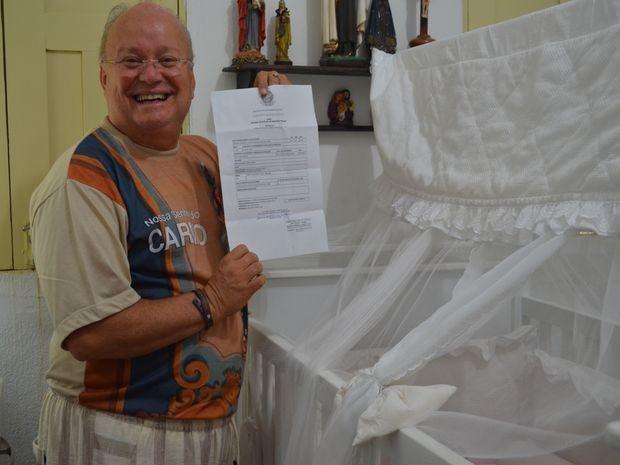 Erundino exibe orgulhoso documentação que legitima como pai (Foto: Flávio Anutes/G1)