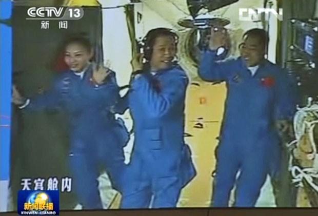 Outa imagem da CCTV mostra os astronautas Wang Yaping, Nie Haisheng e Zhang Xiaoguang já dentro do Tiangong-1. Wang é a segunda mulher chinesa a ser mandada ao espaço (Foto: AFP/CCTV)