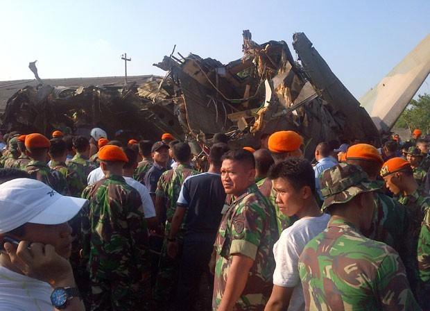 Militares cercam os destroços do avião acidentado nesta quinta-feira (21) na periferia de Jacarta, capital da Indonésia (Foto: AFP)