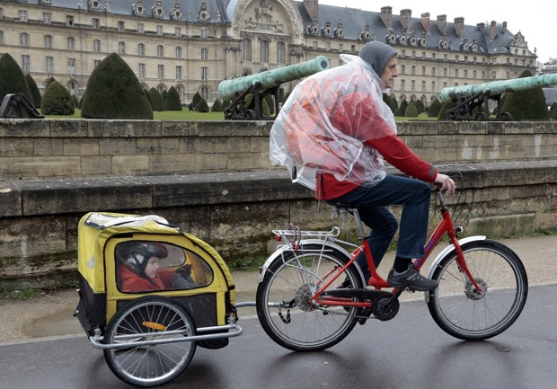 Menino observa paisagem enquanto é levado por ciclista em carruagem minúscula (Foto: Jacques Demarthon/AFP)