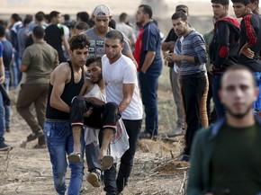 Palestinos carregam um manifestante ferido que foi baleado por soldados israelenses durante confrontos perto da fronteira israelense no nordeste de Gaza. Seis palestinos morreram  (Foto: Mohammed Salem/Reuters)