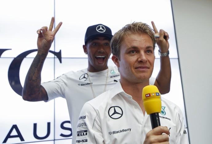 Lewis Hamilton faz graça atrás de Nico Rosberg em evento de patrocinador em Cingapura (Foto: Reuters)