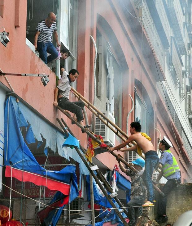 Pessoas são retiradas de prédio em chamas na China; incêndio atingiu creche (Foto: China Daily/Reuters)