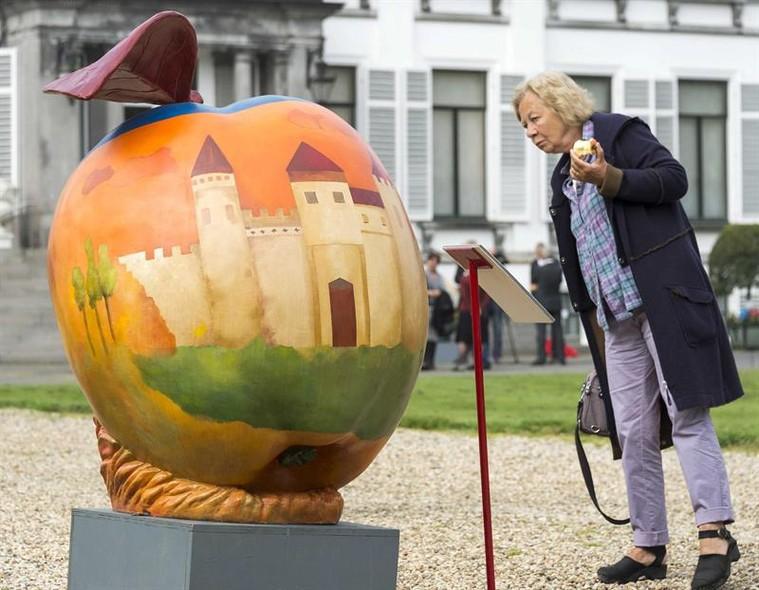 Mulher observa a pintura em uma maça gigante exposta nos jardins do palácio de Soestdijk em Baarn, na Holanda. Uma coleção de 51 maças gigantes inspirada na família real holandesa ficará exposta ao público até dia 31 de agosto