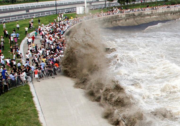 Curiosos foram atingidos por onda ao acompanhar 'pororoca' gigante no rio Qiantang, em Hangzhou (Foto: Reuters)