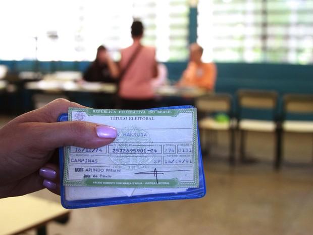 Eleitor mostra título na entrada da sala de votação em Campinas  (Foto: Janaína Ribeiro)