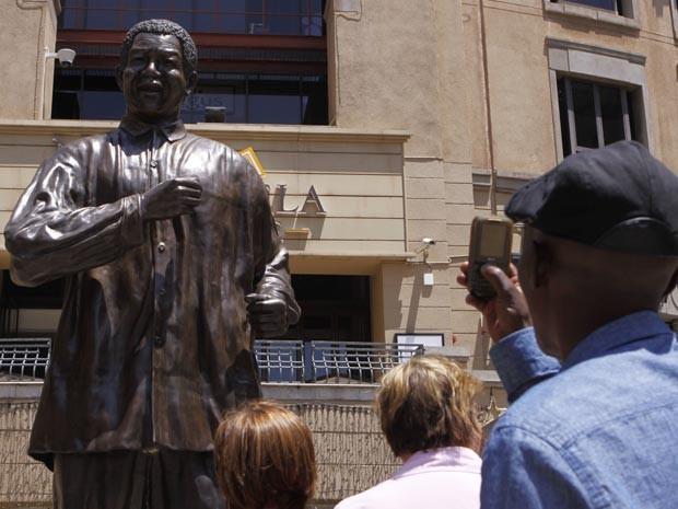 Admirador fotografa estátua na Praça Mandela, em Joanesburgo (Foto: AP Photo/Denis Farrell)
