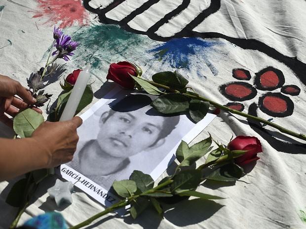 Estudante deposita flores e vela no retrato de um dos estudantes desaparecidos durante protesto na Cidade do México, na quarta-feira (8) (Foto: AFP Photo/Ronaldo Schemidt)