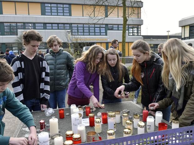 Estudantes da escola alemã Joseph-Koenig acendem velas em homenagem aos colegas mortos (Foto: Martin Meissner/AP)