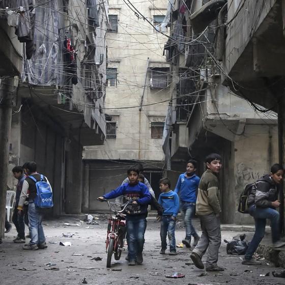 Garotos voltam da escola em rua de alepo, Síria. (Foto: /Komsomolskaya Pravda via AP)