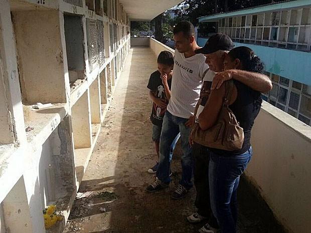 Pai de Paulo Ricardo acende vela no local onde corpo do filho foi enterrado (Foto: Katherine Coutinho / G1)