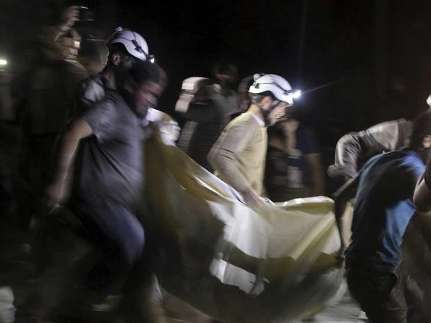 Defesa Civil carrega vítima após ataque aéreo a um hospital em Aleppo (Foto: Abdalrhman Ismail / Reuters)