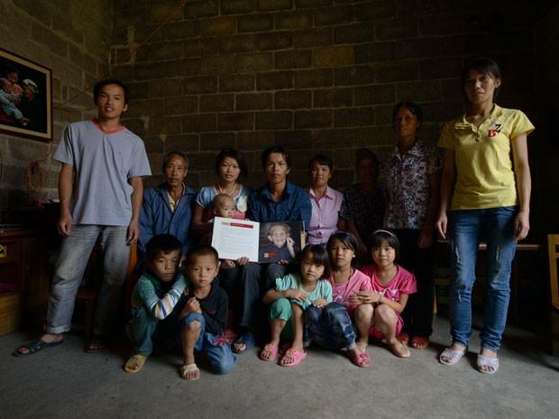 Filhos, netos e bisnetos de Luo Meizhen posam para foto na casa onde a mulher vivia em Longhong, na China (Foto: Ed Jones/AFP)