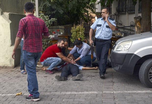 Policial ferido é visto após ataque atribuído ao PKK contra restaurante em Diyarbakir, na Turquia, nesta sexta-feira (11) (Foto: Ilyas Akengin/AFP)