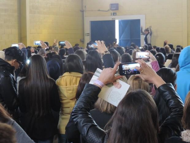 Fiéis pegaram celulares na esperança de fotografarem padre na chegada (Foto: Caio Gomes Silveira/ G1)