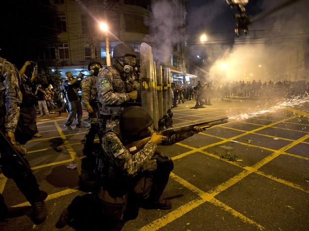 Policial dispara contra manifestantes no Rio de Janeiro (Foto: Silvia Izquierdo/AP)
