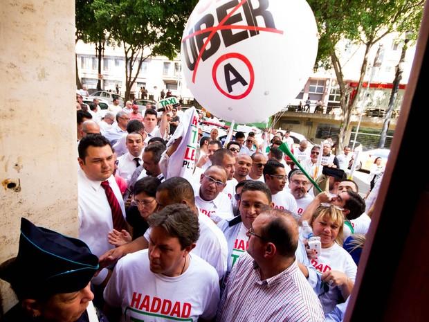 Grupo de taxistas tenta entrar na sede da Prefeitura de São Paulo, no Centro, onde será realizado o anúncio do prefeito Fernando Haddad (PT) sobre a regulamentação do aplicativo Uber na cidade (Foto: Dario Oliveira/Código19/Estadão Conteúdo)
