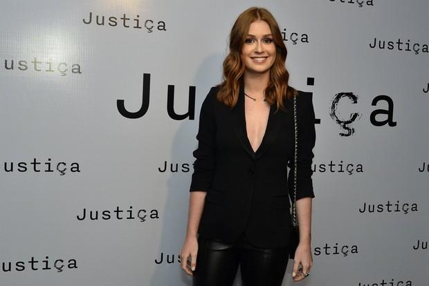 Atriz usando look preto com bolsa transversal em evento da novela Justiça.